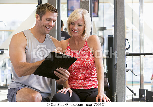 Personal Trainer Talking To Woman At Gym - csp1709131