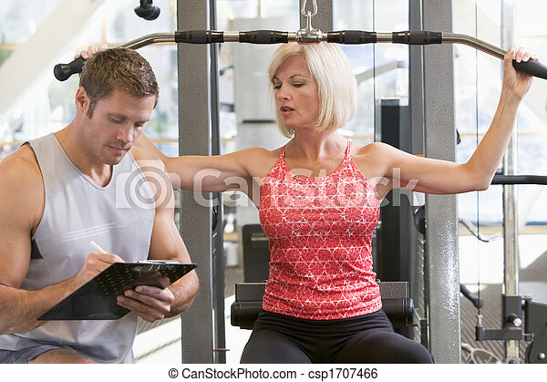 Personal Trainer Watching Woman Weight Train - csp1707466