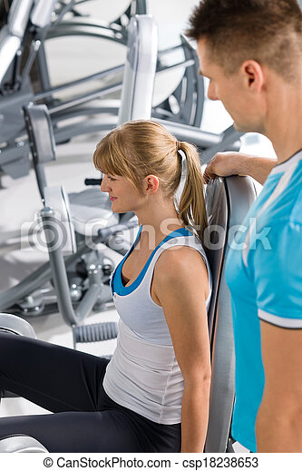 Personal trainer with young woman at gym - csp18238653