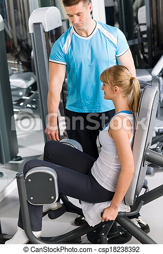 Personal trainer with young woman at gym - csp18238392