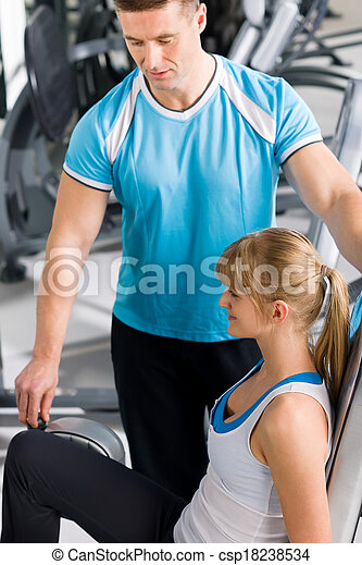 Personal trainer with young woman at gym - csp18238534