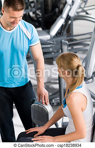 Personal trainer with young woman at gym - csp18238934
