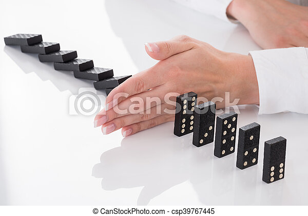 Person's Hand Stopping Dominos Falling On Desk - csp39767445