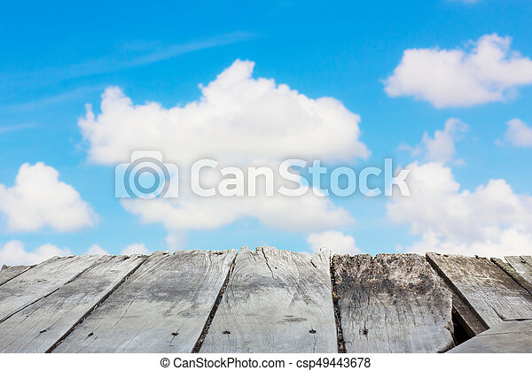 perspective old wooden board empty table in front of blur background of  bright cloudy sky, can be used for display or montage your products  Mock  up