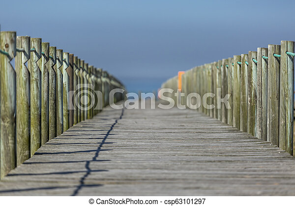 Perspective view of wooden pedestrian walkway, towards the ocean, next to the beach - csp63101297