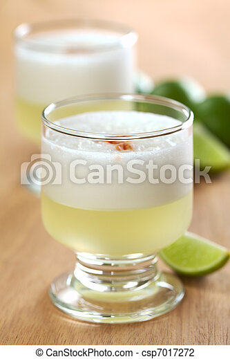 Peruvian cocktail called Pisco Sour made of Pisco (Peruvian grape schnaps), lime juice, syrup and egg white (Selective Focus, Focus on the front glass rim) - csp7017272