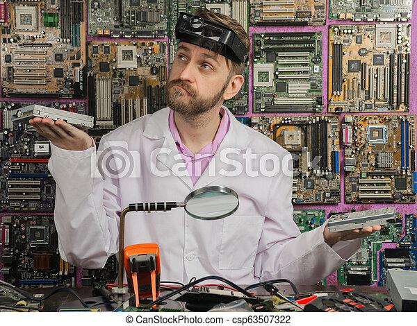El joven ingeniero electricista pesa en las manos del HDD y conduce - csp63507322