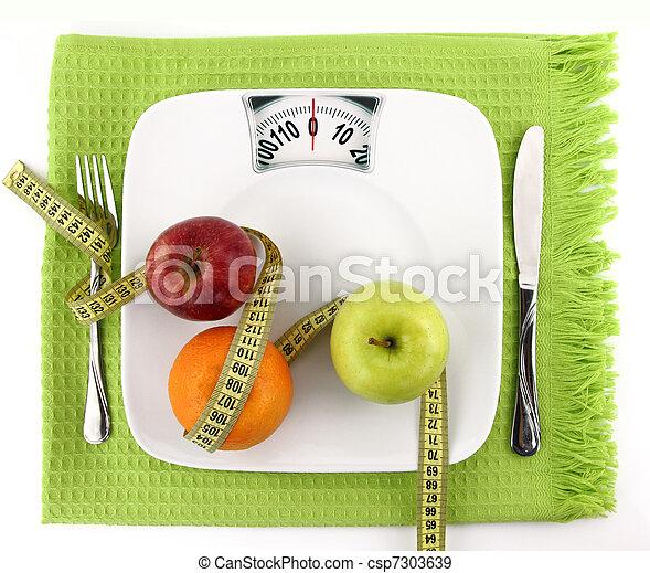 Concepto de dieta. Frutas con cinta de medición en un plato como la escala de peso - csp7303639