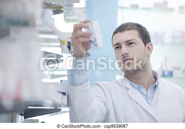 pharmacist chemist man in pharmacy drugstore - csp9539087