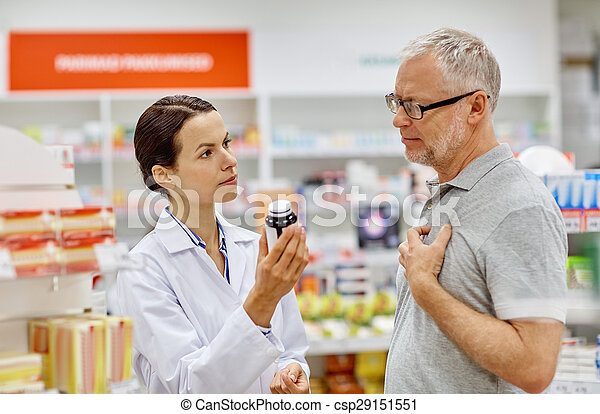pharmacist showing drug to senior man at pharmacy - csp29151551