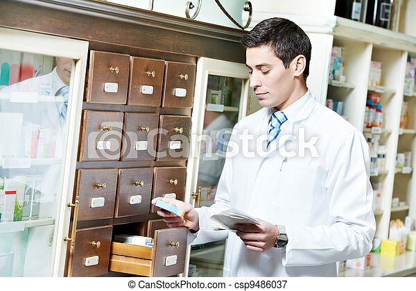 Pharmacy chemist man in drugstore - csp9486037
