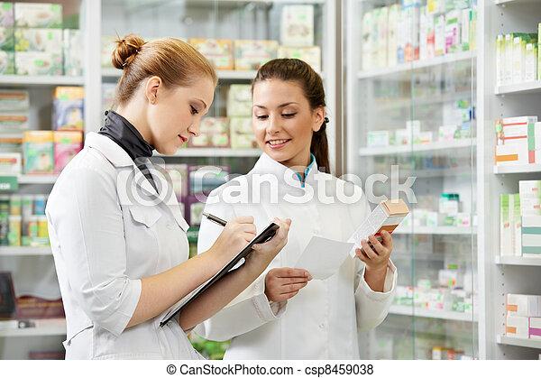 Pharmacy chemist women in drugstore - csp8459038