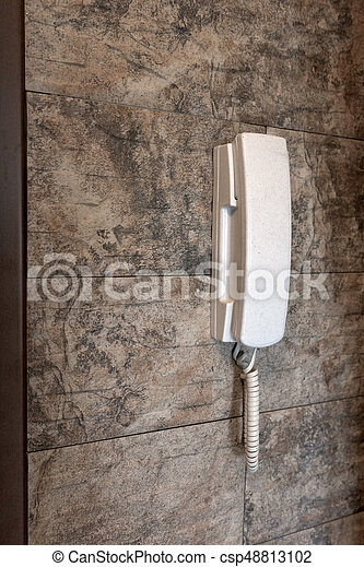phone attached to a stone wall - csp48813102