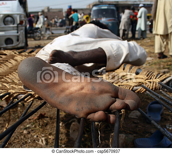 Photo of a man relaxing outdoor, withi his feet dirty from walking barefoot, in Lahore, Punjab, Pakistan - csp5670937