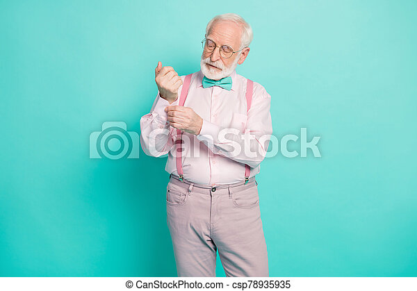 Photo of attractive hipster grandpa preparing senior meeting party buttoning sleeve carefully wear specs pink shirt suspenders bow tie pants isolated teal color background - csp78935935
