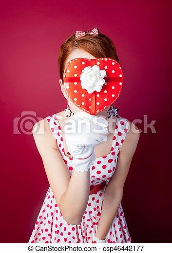 photo of beautiful young woman in vintage dotted dress with cute box on the wonderful burgundy background - csp46442177