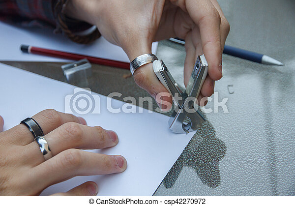 Photo of close up of a hands removing a staple from some documents with a staple remover. - csp42270972