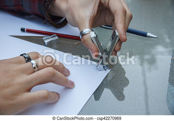 Photo of close up of a hands removing a staple from some documents with a staple remover. - csp42270969