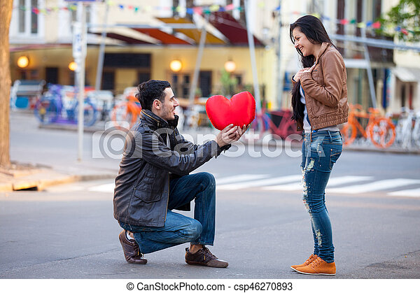photo of cute couple with heart shaped toy on the wonderful street background - csp46270893