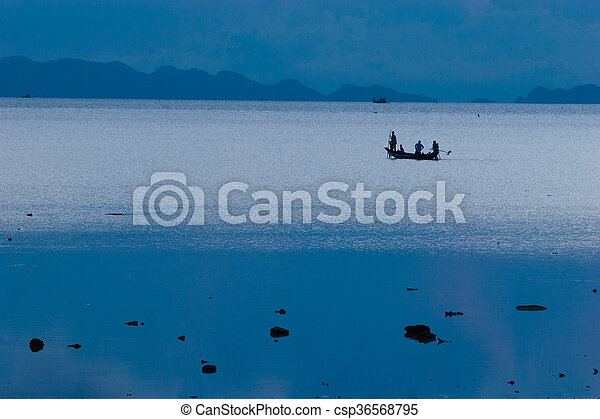 Photo of fishermans in long tail boat tropical beach at sunset. Ko li pe island. Horizontal - csp36568795