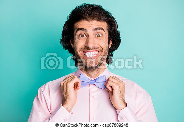 Photo of handsome cute boyfriend wear pink outfit two arms fix bow tie isolated teal color background - csp87809248