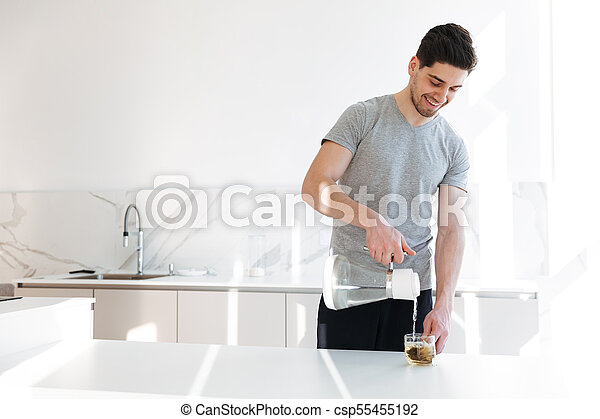 Photo of muscular man in casual t-shirt making tea with pouring hot water into cup, while having breakfast in morning at home - csp55455192