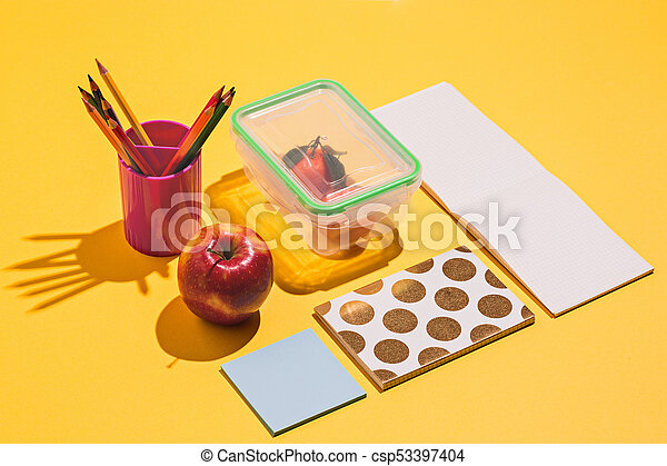 Photo of office and student gear over yellow background - csp53397404