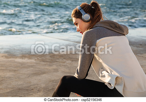 Photo of pretty sport woman listening to music, while resting after run, seaside outdoor