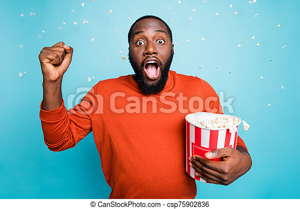 Photo of speechless stunned crazy handsome funny man shocked about plot twist of movie he watches holding bucket isolated in rain of pop corn over blue vivid color background - csp75902836