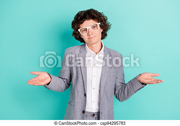 Photo of sweet doubtful school boy wear grey jacket spectacles shrugging shoulders isolated turquoise color background - csp94295783