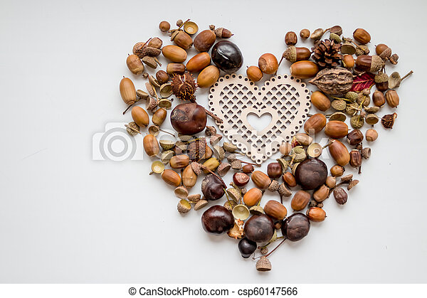 photo of the delicious nuts acorn as heart, heart shaped toy, fir-cones and nuts on the white background. autumn decorations .Copy space - csp60147566
