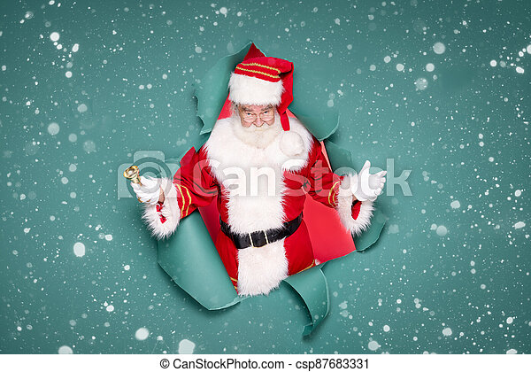 Photo of traditional Santa Claus ringing on a gold bell. - csp87683331