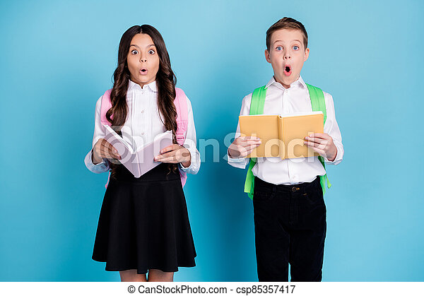 Photo of two small girl boy schoolkids classmates hold copybook open mouth shock read incredible history facts wear bag white shirt black pants dress isolated blue color background - csp85357417