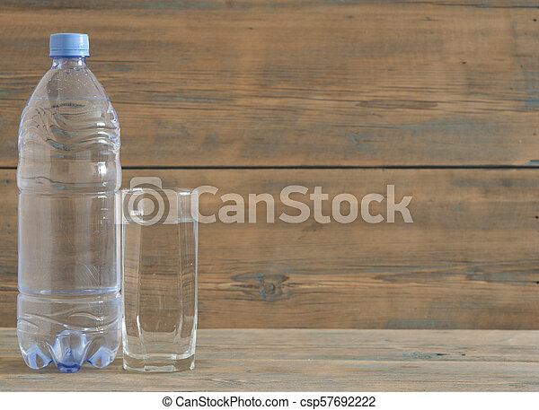 photo of water bottle with glass on wooden table - csp57692222