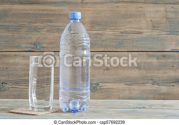 photo of water bottle with glass on wooden table - csp57692239