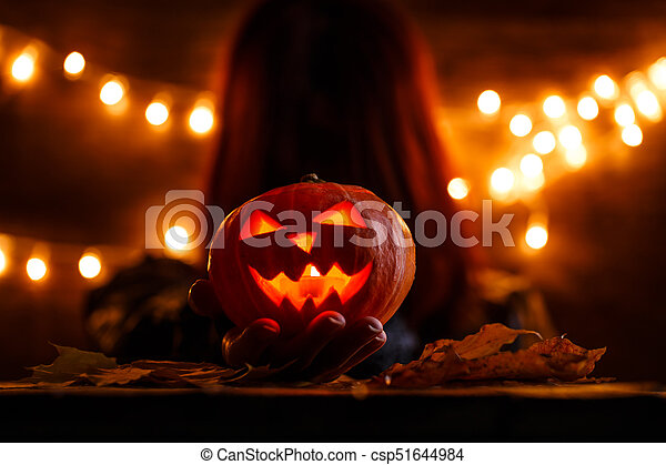 Photo of witch with long hair holding pumpkin - csp51644984
