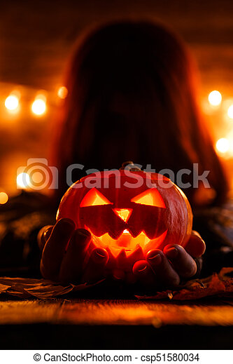 Photo of witch with long hair holding pumpkin - csp51580034