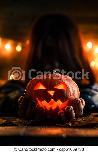 Photo of witch with long hair holding pumpkin - csp51669738