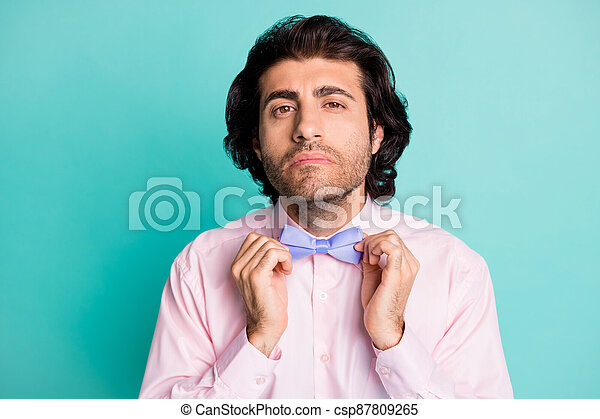 Photo portrait of handsome gentle man dressed pink outfit preparing date fixing bow tie isolated teal color background - csp87809265