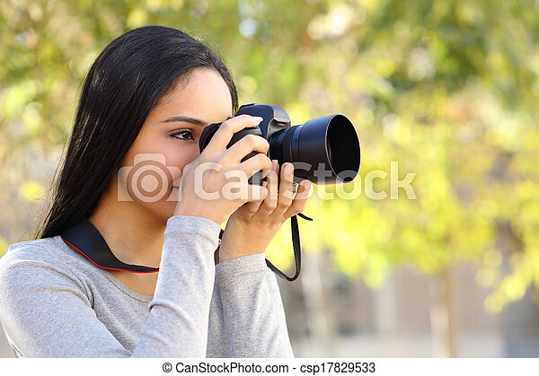Photograph woman learning photography in a park - csp17829533