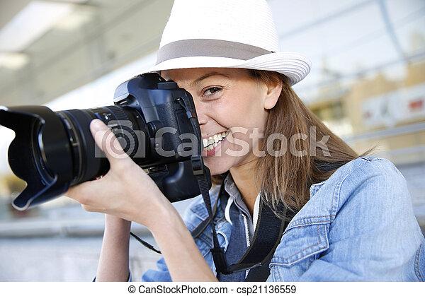 Photographer capturing photo with professional camera - csp21136559