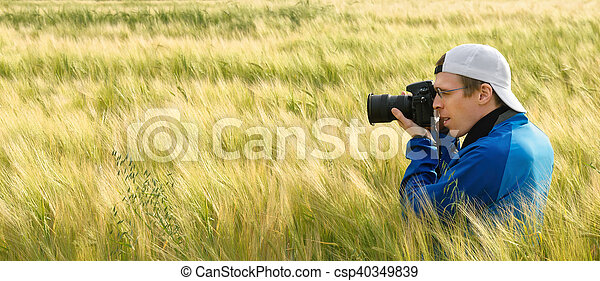 Photographer in a field of barley - csp40349839