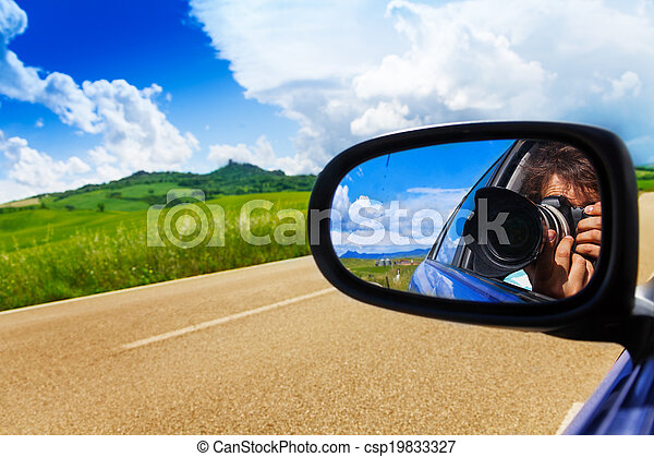 Photographer in car mirror drives near valley - csp19833327