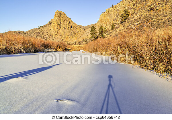 photographing winter sunset in mountains - csp64656742