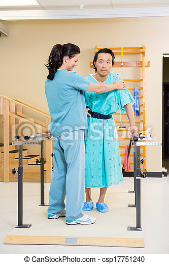 Physical Therapist Assisting Male Patient In Walking - csp17751240