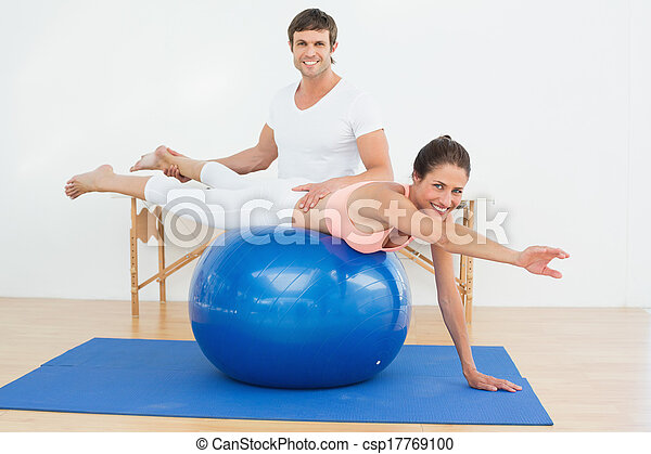Physical therapist assisting woman with yoga ball - csp17769100