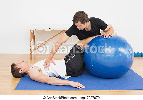 Physical therapist assisting young man with yoga ball - csp17227079