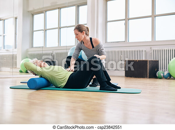 Physical therapist helping elder woman at gym - csp23842551