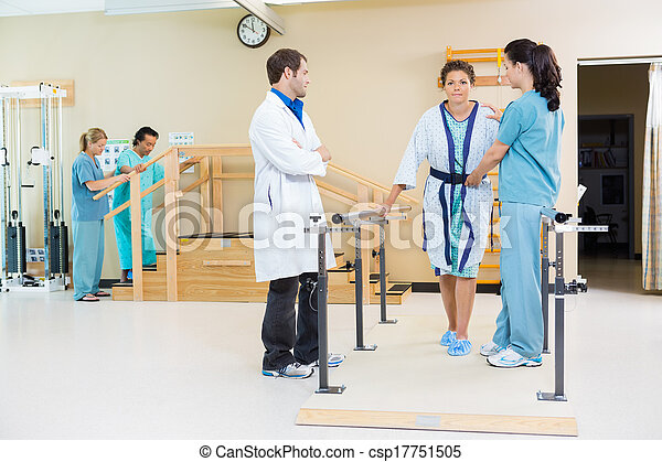 Physical Therapists Assisting Female Patient In Walking - csp17751505