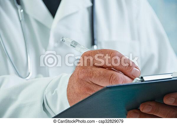 Physician writes medical records - csp32829079